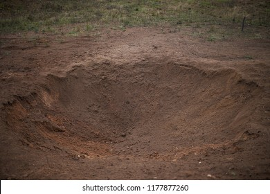 place of hostilities, crater from explosion of destroyed explosives, the pit in the ground strewn with soil after the explosion of the projectile, detonation of mines or crater from the bombing, war