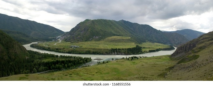 The place of the merge of the famous altai rivers - the wide Katun River skirting the mountain, on the left Samuta flows. Panorama of the Katun River valley on a gloomy cloudy day