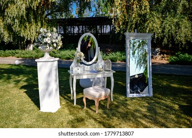 Place for a photo for the bride. White luxury chair stands before a mirror and wedding flower arrangements on the green lawn outside