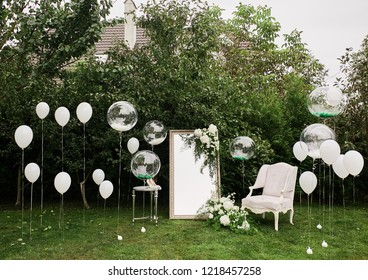 Place for photos at the wedding. White luxury chair stands before a mirror and balloons on the green lawn outside