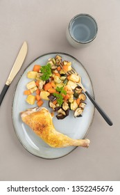 Place setting chicken dinner with oven roasted chicken leg and roasted vegetables