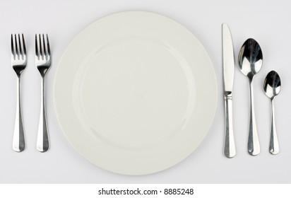 A place setting for a dinner against a white tablecloth