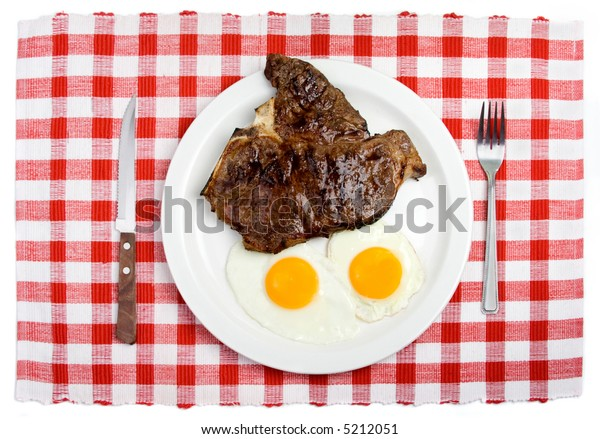 A place setting with a plate of two sunny-side up eggs and a T-bone steak.
