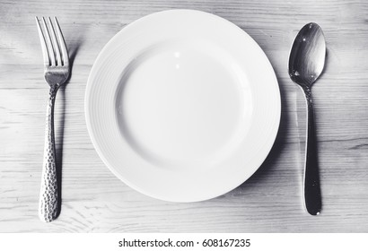 Place setting with plate,fork and spoon on wooden background.black and white tone.