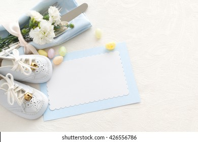 Place setting of Silverware, Baby Shoes, Candy, pastel blue napkin, blank name card, and flowers on side on white tablecloth with room or space for copy, text, your words. Horizontal top aerial view