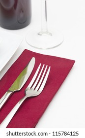 Place setting with white plates and red wine with red napkin