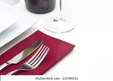 Place setting with white plates and red wine and red napkin