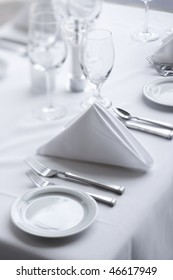 Place settings on an elegant, white dining table in a restaurant. Vertical shot.