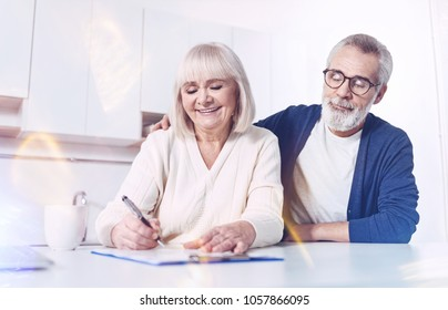 Place for signature. Cheerful delighted old couple sitting in the kitchen and signing the insurance contract while expressing positivity