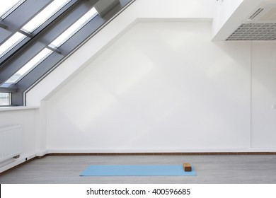 A place for sports training. Mat and supporting unit for yoga and fitness lying on the floor. The room is flooded with daylight sunlight from the window, the glare on the wall.