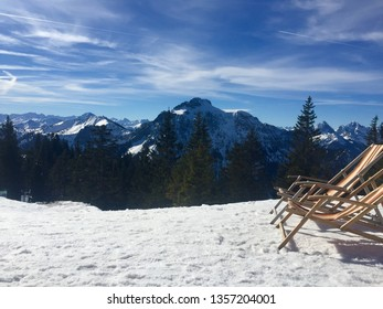 A place in the sun: Panorama view from Tegelberg to the Alps landscape. Sunny winter day, snow, sun bath, mountains, blue sky, skiing, hiking in the snow (Schwangau, Allgäu, Allgau, Bavaria, Germany)