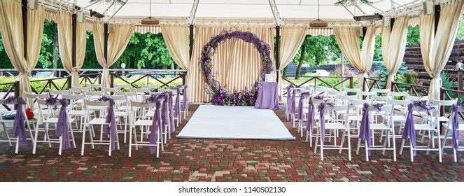 Place for wedding ceremony with wedding arch decorated with violet flowers and white chairs on each side of archway outdoors, copy space. Empty wooden chairs for guests