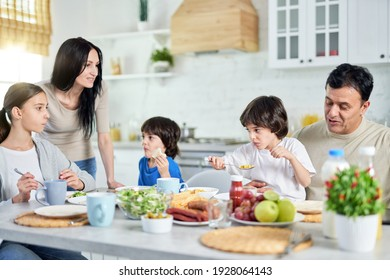 A place where family unites. Loving hispanic parents taking care of their little children while having lunch together at home