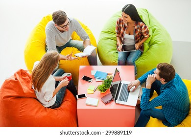 Place where ideas born. Top view of four young people working together while sitting at the colorful bean bags