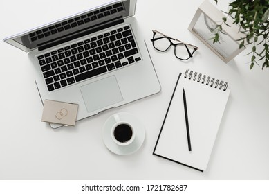A place to work. Work desk, coffee on the table, glasses, notebook for writing notes. White background, minimalism empty space for notes.