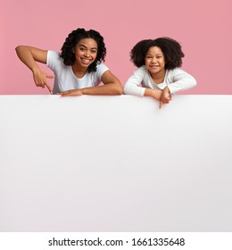 Place For Your Ad. Happy Afro Mom And Daughter Leaning And Pointing At Blank White Advertisement Board Over Pink Background, Copy Space