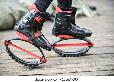 Place your feet in the kangoo-style jumping shoes. Girl doing sport exercises kangoo