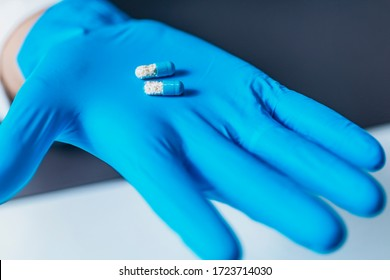 Placebo drug concept. Hand in gloves showing two identical pills with different contents, one real, one placebo