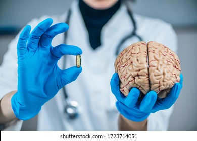 Placebo Effect Concept. Female doctor holding model of brain and placebo supplement pill, explaining the placebo effect healing phenomenon