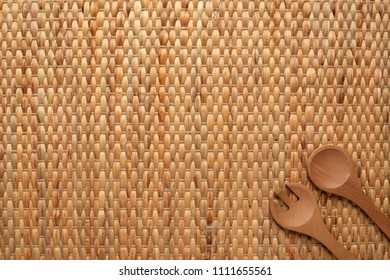 A placemat background showing texture of dried water hyacinth with wooden spoon and fork at the corner with copy space.