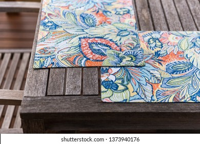 Placemats set on outdoor wooden table.