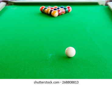 Placement of billiard balls on the table before the game. Focus on white ball.