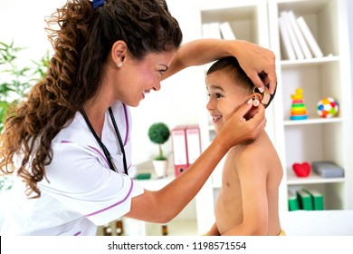 Placement of the hearing aid medical device on child's ear done by his doctor