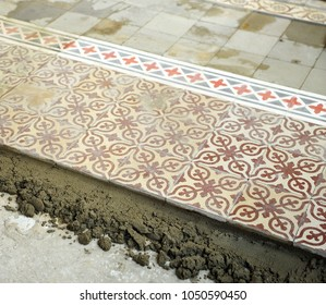 Placement of a pavement of hydraulic tiles that form a mosaic, vintage decoration that is back in fashion, Seville, Spain