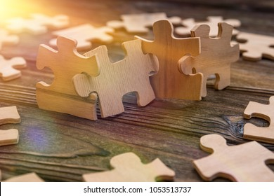 Placement of puzzle pieces in a row on a textured rustic wooden table. Concept business, teamwork and cooperation, strategy, cooperation