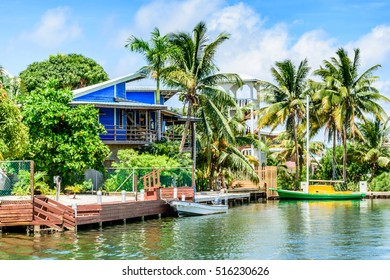 Placencia, Belize - August 28, 2016: Tropical waterside house with moored boats on lagoon side of Placencia in Belize, Central America