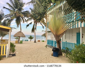 Placencia, Belize - May 26th, 2018: Beautiful sandy beach with a beach house surrounded by sand and flowers in the tropical town of Placencia, Belize