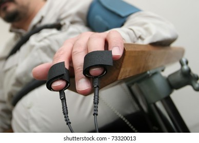 Placing equipment for interrogation of a man with lie detector. Electrodes attached to fingers