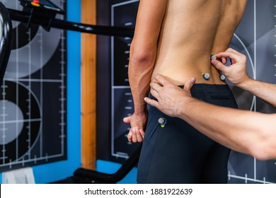 Placing markers on mans lower back for 3D gait test in anthropometry laboratory