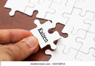 Placing missing a piece of puzzle with kaizen (continuous improvement) word