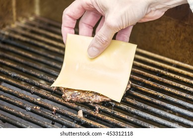 Placing a slice of American cheese on a grilled hamburger patty