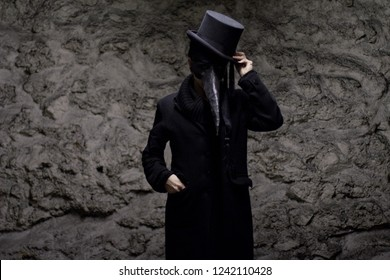 Plague doctor, all dressed in black, with the beak mask, holding his hat like a salute. Grey texture background behind