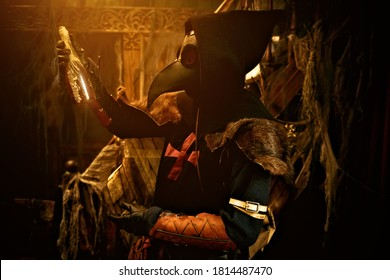 The plague doctor is holding a bottle of medicine for the plague bubonic plague. The atmosphere of mysticism. Historical reenactment. Halloween.