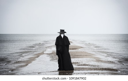 Plague doctor in seaside. Outdoor portrait with dramatic sky in background.