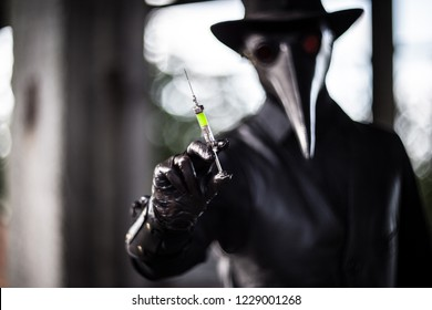 Plague doctor shows a syringe with a poisonous green liquid. Authentic glass syringe with a poison is in focus.