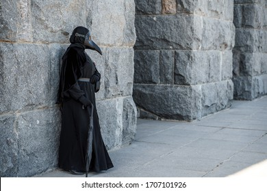 plague doctor stands against a stone wall