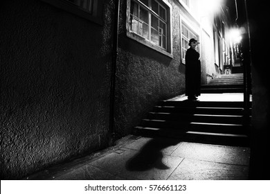 The Plague Doctor in the streets of Old Town, just off Royal Mile in the closes of Edinburgh, Scotland. Spooky character. Black and white photograph with games of shadows and lights.