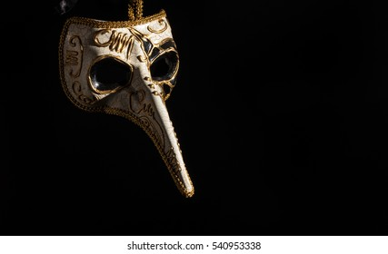 Plague mask hanging isolated on a black background