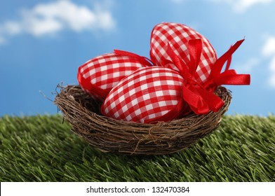 Plaid Easter eggs in nest on grass field