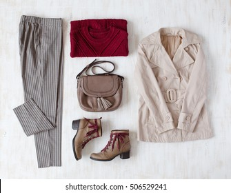 Plaid pants, dark red oversize knitted sweater, small brown leather bag, brown leather ankle boots, beige coat on white wooden background. Overhead view of woman's casual outfits. Trendy autumn look.