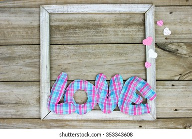 Plaid pink and blue fabric word LOVE and hearts on wooden rustic frame background