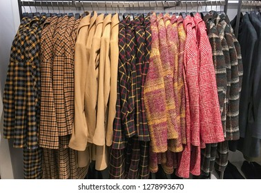 plaid shirts in different colors sundress, jacket ,coat on hangers in a retail shop