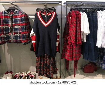 plaid shirts in different colors sundress, jacket ,coat, jeans, shoes on hangers in a retail shop