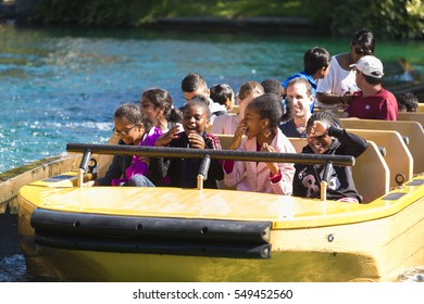 PLAILLY, FRANCE - JULY 10, 2015: Some girls smile into a barge in an amusement park.
