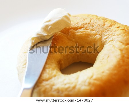 Plain bagel, knife, and kitschy-looking cream cheese against white background.
