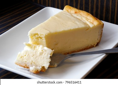 Plain baked cheesecake with cake on fork on white ceramic plate. Brown background.